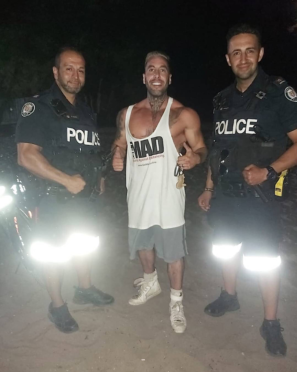 Toronto police is investigating this photo of two officers with Chris Sky (Instagram - @meet.the.skys)